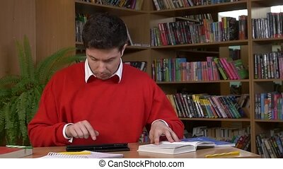 Student using his digital tablet in a library, slow motion -...