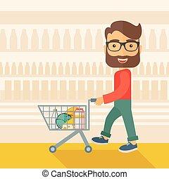 Male Shopper Pushing a Shopping Cart - A male shopper...