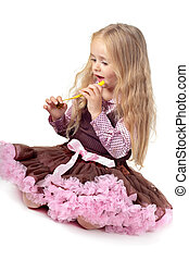 Girl in tutu skirt playing with party blower