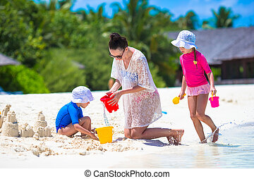 Adorable little girls and happy mother playing with beach...
