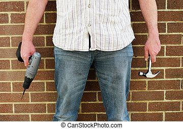 Man holding a drill and hammer