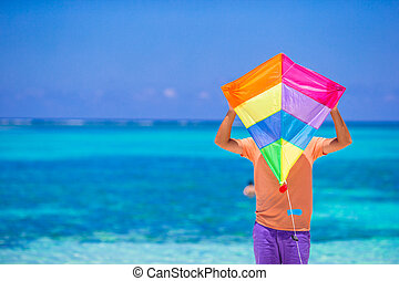 Young man with a kite on a background of turquoise sea - A...