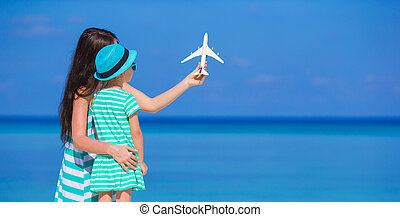 Young woman and little girl with miniature of airplane at...