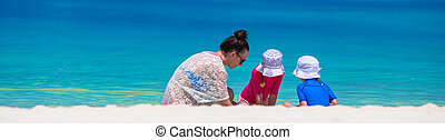 Young mom and little girls playing on white sandy beach -...
