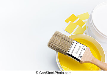 brush over can of yellow paint - newly opened can of yellow...