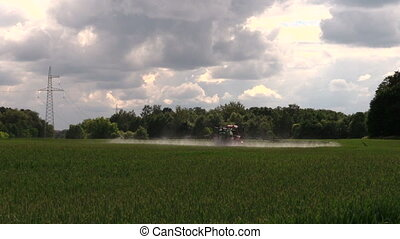 tractor crop pesticide - farm tractor spraying wheat field...