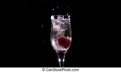 Strawberry splash in a champagne flute. Slow motion. -...