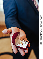 Groom holds a jewelry gift box with gold wedding rings. Man...