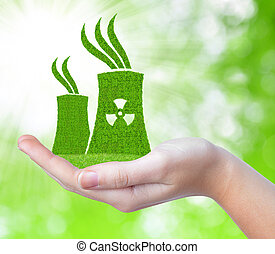 Nuclear power plant icon in hand on green natural...