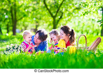 Young family with kids having picnic outdoors Parents with...