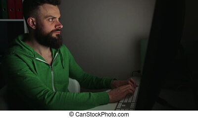 Beared man using computer - Beared man working at a computer