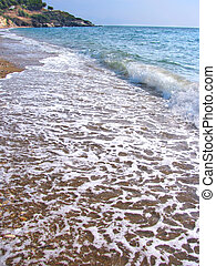 Gentle tide - Small wave gently swapping on sandy beach