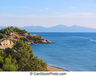 Coast of Mediterranean sea. Beach and rocky wooded shore