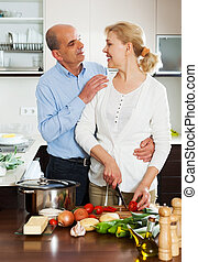 Elderly couple cooking salad at home kitchen