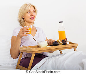 Mature woman eating orange juice, berries and yogurt