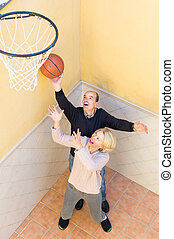 Mature couple playing basketball in patio - Happy smiling...