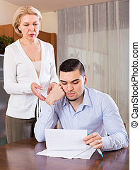 Adult son and senior mother with papers - Financial crisis...