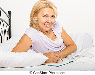 mature woman writing in diary and laying in bed at home