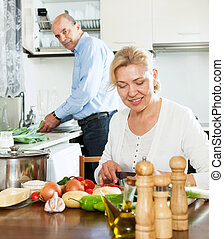 elderly man and mature woman doing housework together
