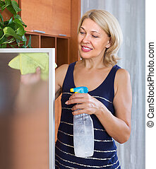 Mature woman cleaning glass door - Mature smiling blonde...