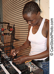 african woman working on machine - an african woman working...