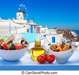 Greek salad against windmill in Oia village, Santorini...