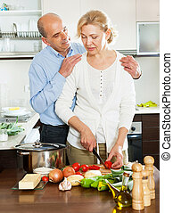 mature couple cooking together in  kitchen