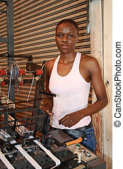 african female worker - an african female worker standing by...