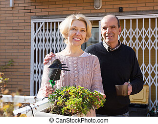 Mature cuople talking at balcon - Mature woman talking with...