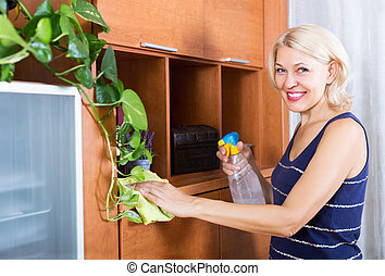 Smiling woman dusting wooden furniture with rag and cleanser...