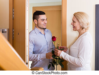 man and woman standing at doorway - Happy handsome man and...