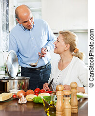 Senior couple preparing a healthy lunch in their kitchen -...