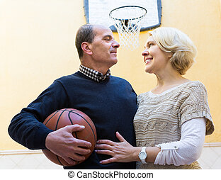 Mature couple playing basketball in patio - Happy active...