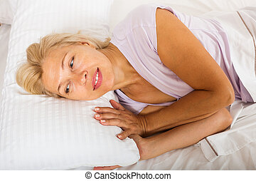 mature woman in shirt laying on bed at bedroom