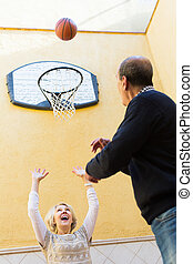 Mature couple playing basketball in patio - Cheerful smiling...
