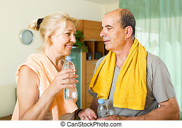Pensioners with water after fitness - Smiling elderly...