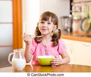 kid eating healthy food in kitchen - kid girl eating healthy...