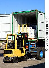 forklift loading truck - a forklift loading goods onto a...