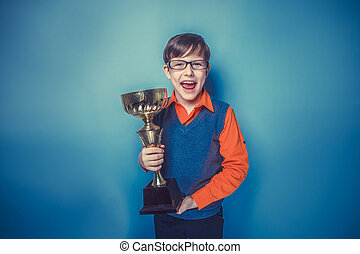European -looking boy of ten years in glasses holding a cup,...
