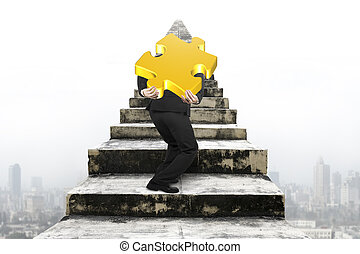 Businessman carrying gold jigsaw puzzle on old stairs with...
