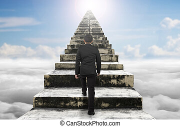 Businessman climbing the old concrete stairs with cloudscape...
