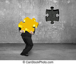 Businessman carrying 3D gold jigsaw puzzle piece to insert...