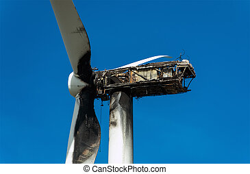 View of Burned wind turbine over blue sky.
