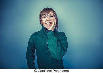 happy teenager boy twelve years in glasses on gray...