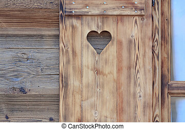 Window blind of a wooden hut with a heart shaped hole