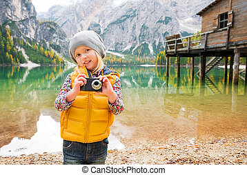 Young blonde girl on shores of Lake Bries holding a camera -...