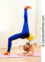 backbend - Slender athletic girl doing yoga exercises indoor...