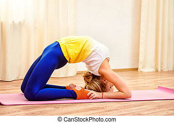 training yoga - Slender athletic girl doing yoga exercises...