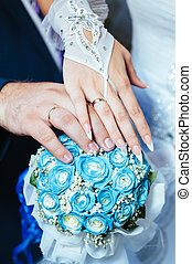 Wedding couple holding hands on wedding bouquet