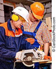 Group people builder with circular saw . - Two men builder...
